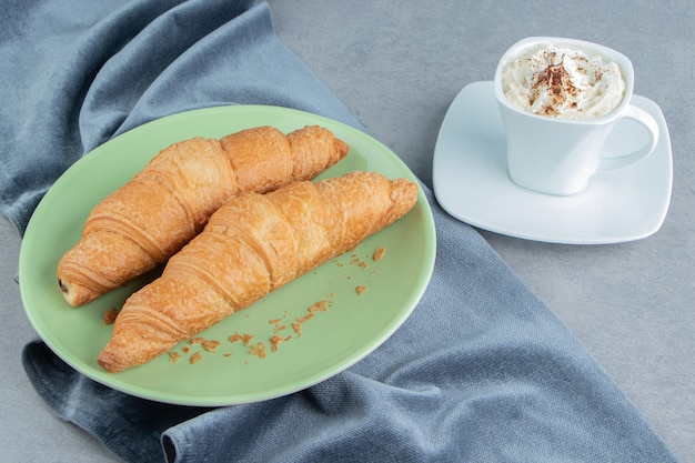 Un affichage de croissant en assiette sur une serviette et avec du café, sur le fond de marbre. photo de haute qualité