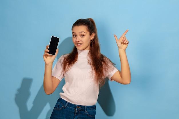 Affichage de l'écran du téléphone, pointant vers le haut. portrait de l'adolescente caucasienne sur fond bleu. beau modèle en tenue décontractée. concept d'émotions humaines, expression faciale, ventes, publicité. copyspace. semble heureux.