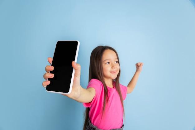 Affichage de l'écran du téléphone. portrait de petite fille caucasienne sur mur bleu.