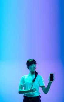 Affichage de l'écran du téléphone vide portrait de jeune femme asiatique sur studio bluepurple dégradé