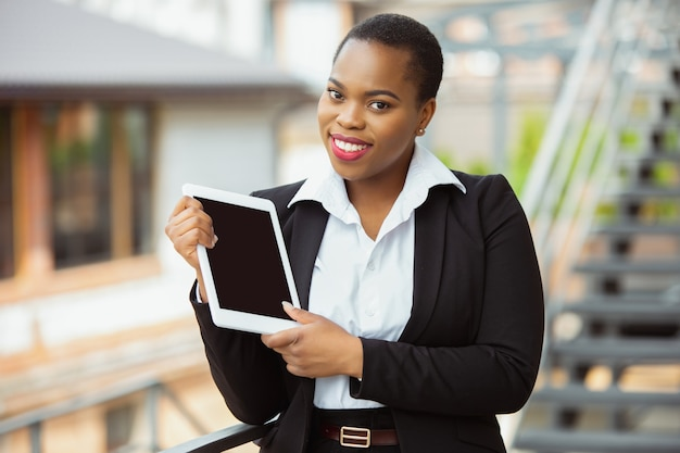 Affichage de l'écran de la tablette vide. femme d'affaires afro-américaine en tenue de bureau souriante, a l'air confiante, occupée. finances, affaires, égalité, concept des droits de l'homme. belle jeune femme modèle, réussie.