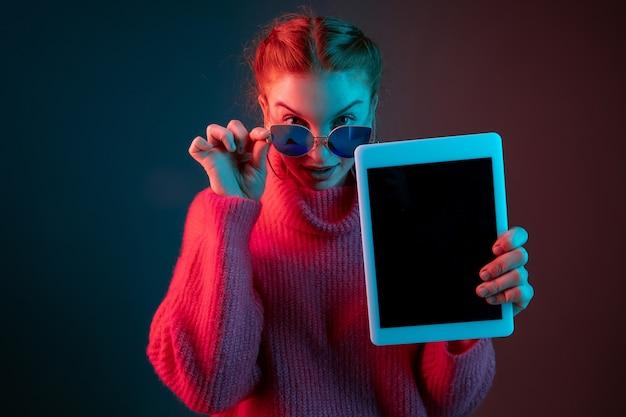 Affichage de l'écran de la tablette vierge portrait de femme caucasienne isolée sur gradient studio