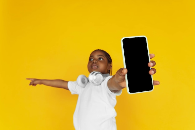 Affichage de l'écran des téléphones vides pointant vers le portrait de petites filles afro-américaines sur jaune