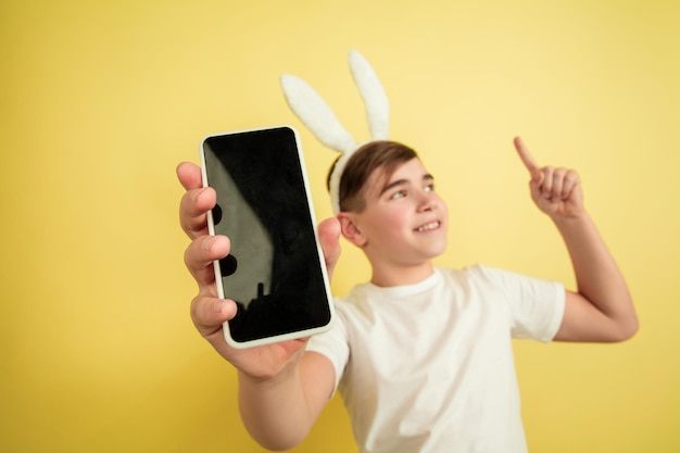 Affichage d'un écran vide, pointant vers le haut. garçon caucasien comme lapin de pâques sur fond jaune. bonnes salutations de pâques.