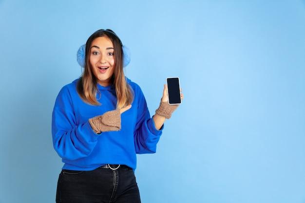 Affichage d'un écran vide. portrait de femme caucasienne sur fond bleu studio. beau modèle féminin dans des vêtements chauds. concept d'émotions humaines, expression faciale, ventes, publicité. humeur hivernale.