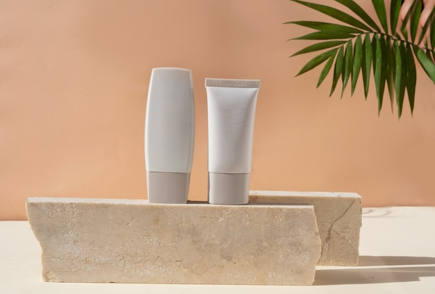 Affichage minimal des produits cosmétiques modernes avec deux tubes sur fond beige avec superposition d'ombre