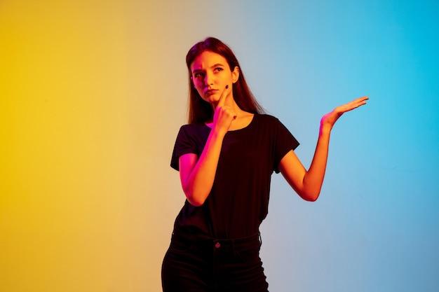 Affichage. portrait de jeune femme caucasienne sur fond de studio bleu-jaune dégradé à la lumière du néon. concept de jeunesse, émotions humaines, expression faciale, ventes, publicité. beau modèle brune.