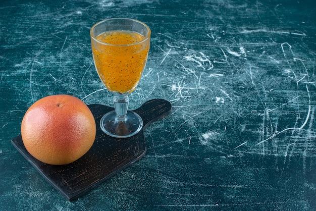 Un affichage d'un verre de jus de fruits et de pamplemousse sur le fond bleu. photo de haute qualité