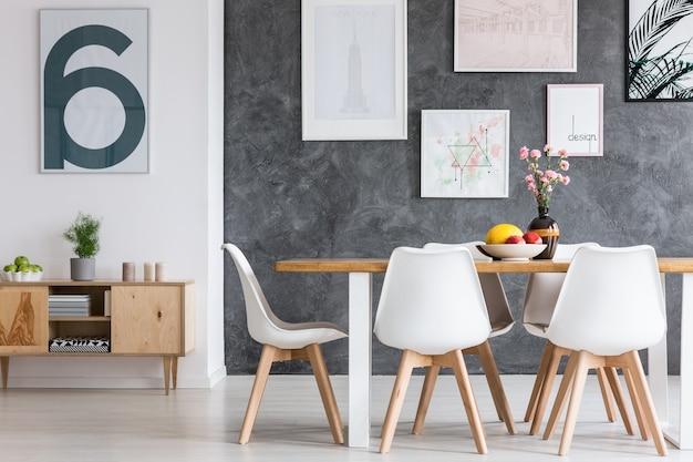 Affiche blanche avec lettre sombre au-dessus d'une armoire en bois classique avec plante dans une salle à manger confortable
