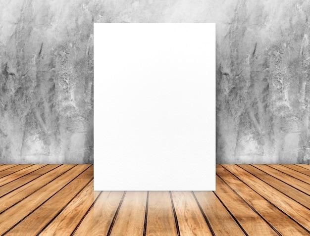 Affiche blanche vierge se penchant au mur de béton sur le plancher en bois,