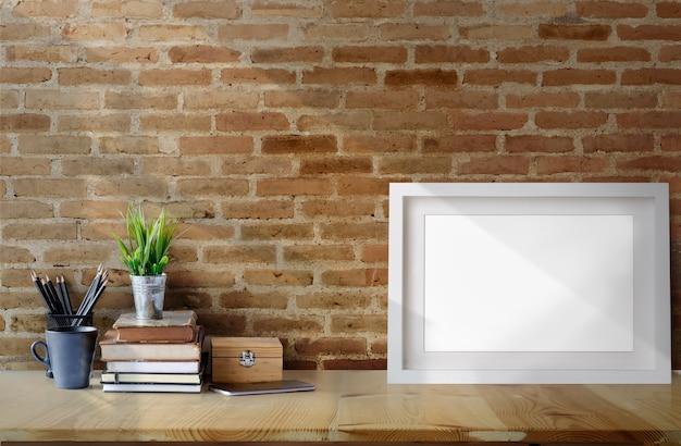 Affiche cadre vierge sur table de travail du bois