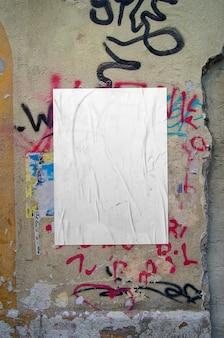 Affiche froissée sur mur de graffitis