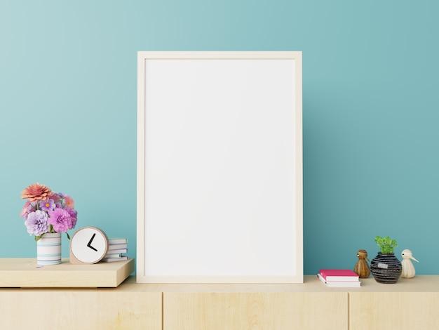 Affiche maquette blanc vertical sur meuble tv sur fond de mur bleu