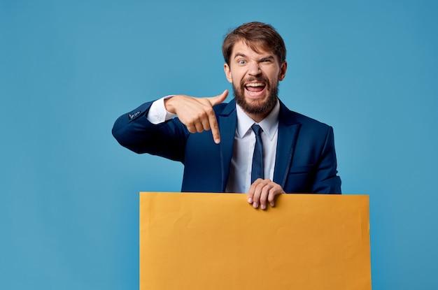 Affiche de maquette jaune homme barbu sur fond bleu à la main. photo de haute qualité