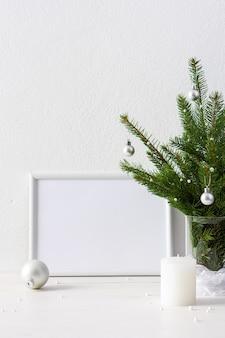 Affiche de noël maquette avec cadre horizontal, branches de sapin dans un vase et boules avec des bougies sur fond de mur blanc, concept de nouvel an et de noël