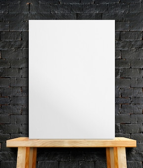 Affiche de papier blanc vierge sur une table en bois au mur de pierre noire