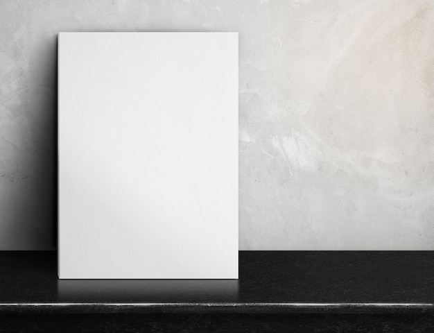Affiche de papier blanc vierge sur une table de marbre noir au mur de béton gris