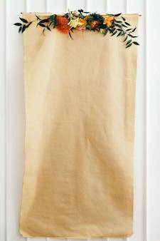 Affiche de papier craft vierge floral sur un mur blanc
