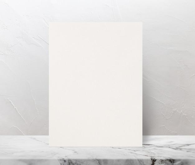 Affiche de papier texturé eco blanc sur le dessus de table en pierre marbre au fond du mur blanc.