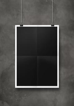 Affiche pliée noire accrochée à un mur de béton avec des clips