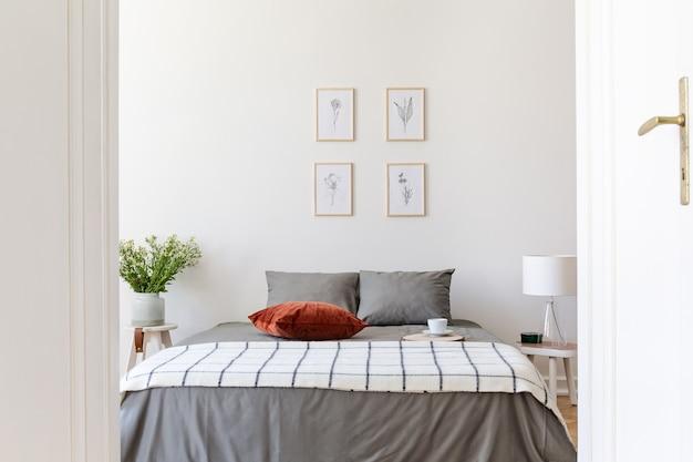 Affiches au-dessus du lit gris avec couverture à motifs et oreiller rouge à l'intérieur de la chambre blanche. vrai photo
