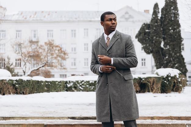 Africain - homme d'affaires américain utilisant un smartphone dans une rue enneigée en hiver