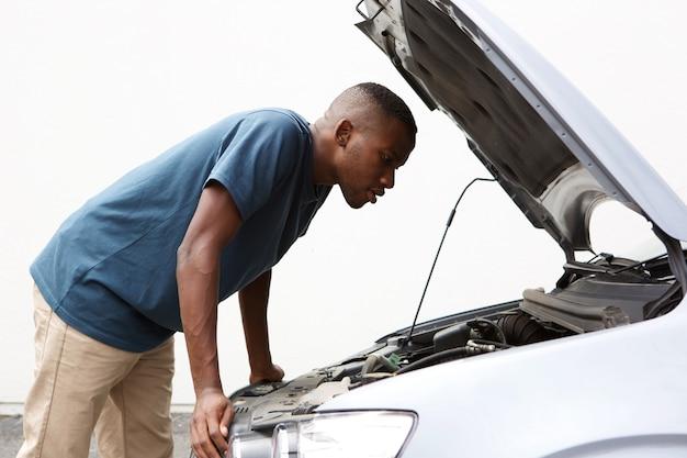 Un africain regardant sous le capot de sa voiture en panne