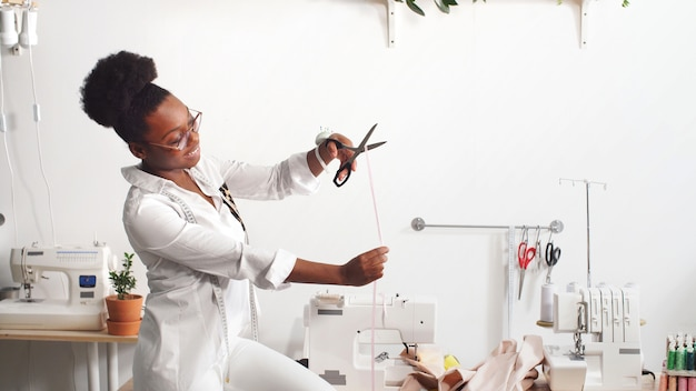 African american female designer de mode professionnelle travaillant sur le tissu dans un atelier