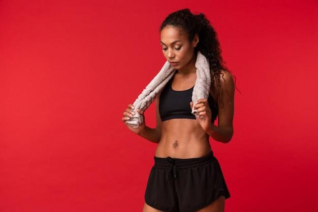 African american fitness girl 20 s en sportswear noir avec une serviette sur son cou debout, isolé sur mur rouge