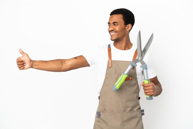 African american gardener man holding sécateur sur fond blanc isolé donnant un coup de pouce geste