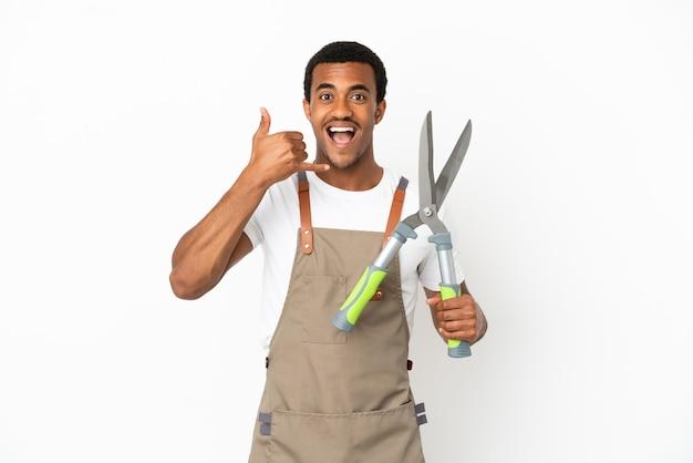 African american gardener man holding sécateur sur fond blanc isolé faisant un geste de téléphone. rappelle-moi signe