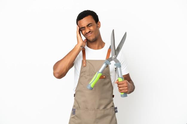 African american gardener man holding sécateur sur fond blanc isolé avec des maux de tête