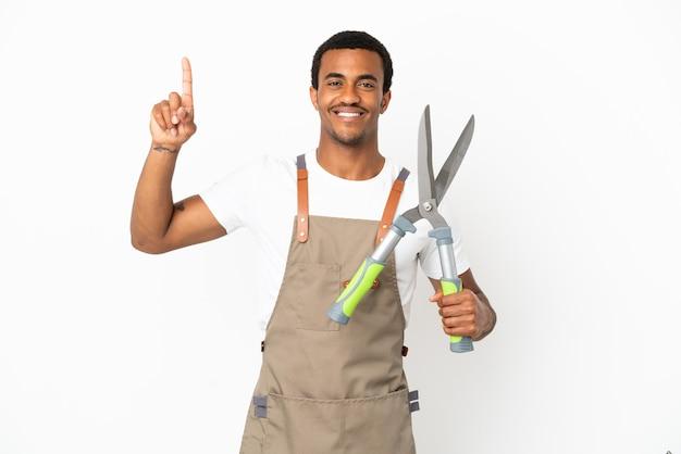 African american gardener man holding sécateur sur fond blanc isolé pointant vers une excellente idée