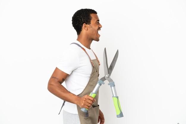 African american gardener man holding sécateur sur fond blanc isolé en riant en position latérale