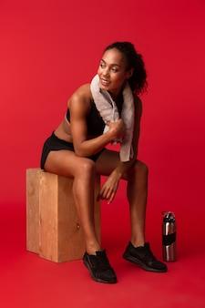 African american healthy girl 20s en vêtements de sport noir assis avec une serviette et une bouteille d'eau sur la boîte, isolé sur mur rouge