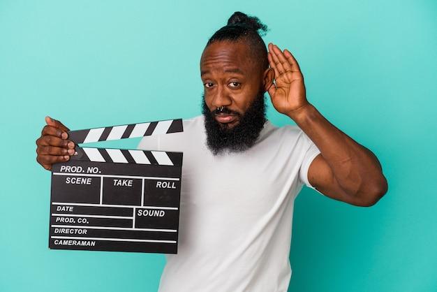 African american man holding clap isolé sur fond bleu essayant d'écouter un potin.
