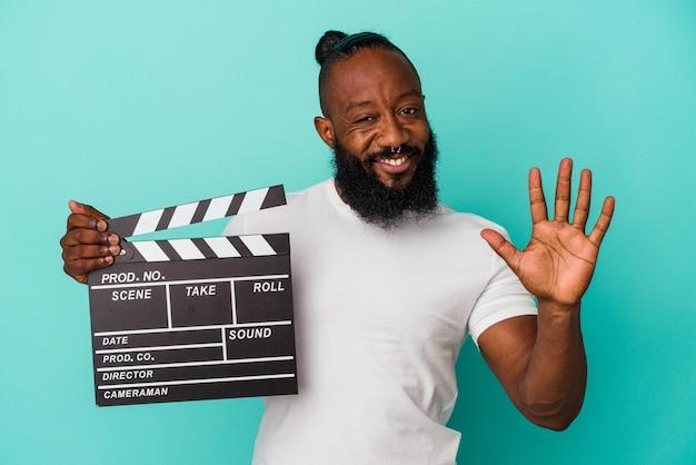 African american man holding clap isolé sur fond bleu souriant joyeux montrant le numéro cinq avec les doigts.