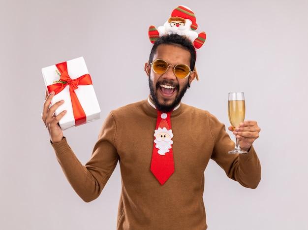 African american man in brown pull et santa rim sur la tête avec une cravate rouge drôle tenant un cadeau et un verre de champagne hurlant excité et heureux debout sur fond blanc