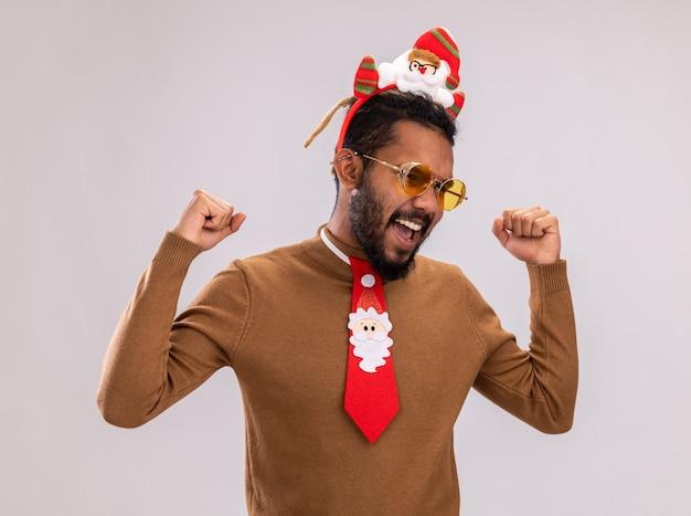 African american man in brown pull et santa rim sur la tête avec drôle cravate rouge serrant les poings heureux et excité debout sur fond blanc