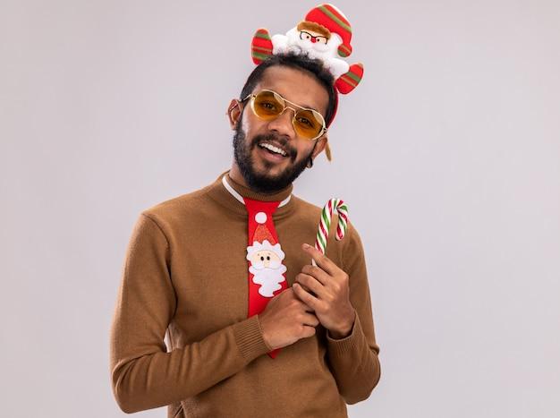 African american man in brown pull et santa rim sur la tête avec drôle cravate rouge tenant la canne à sucre regardant la caméra avec le sourire sur le visage debout sur fond blanc