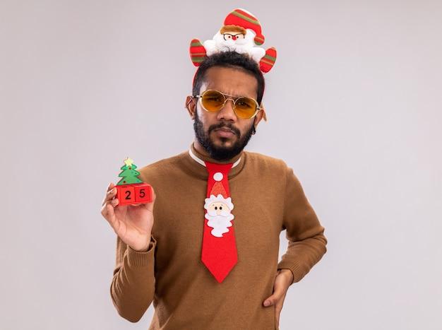 African american man in brown pull et santa rim sur la tête avec drôle cravate rouge tenant des cubes de jouet avec date vingt-cinq regardant la caméra avec un visage sérieux debout sur fond blanc