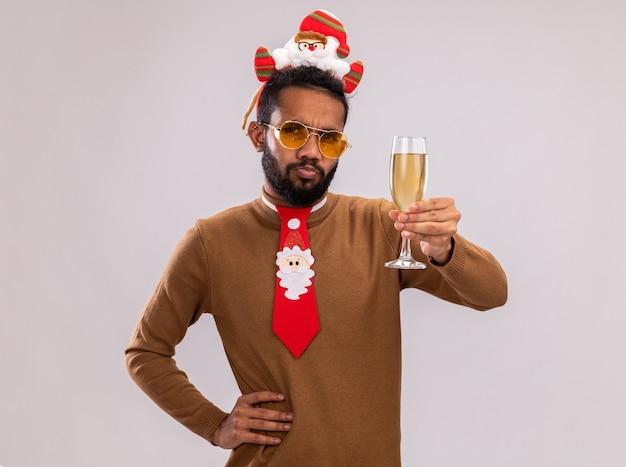 African american man in brown pull et santa rim sur la tête avec drôle cravate rouge tenant un verre de champagne regardant la caméra avec le visage fronçant les sourcils debout sur fond blanc