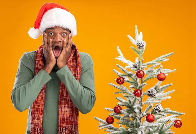 African american man in santa hat et écharpe autour du cou choqué debout à côté d'un arbre de noël sur mur orange