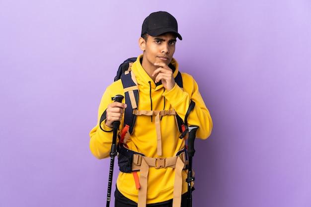 African american man avec sac à dos et bâtons de randonnée sur fond isolé en pensant à une idée tout en regardant