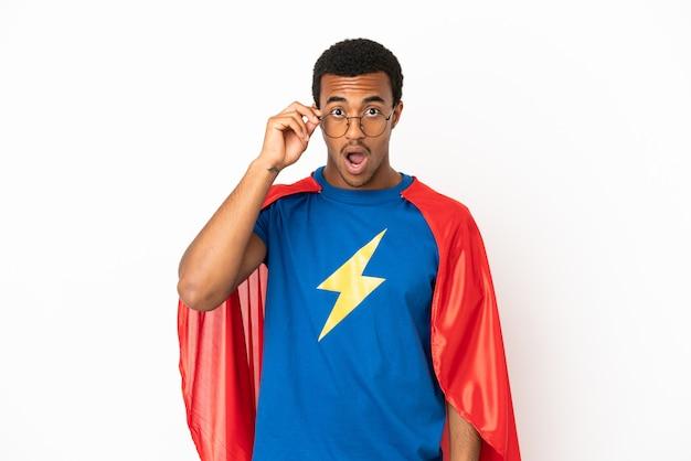 African american super hero man sur fond blanc isolé avec des lunettes et surpris