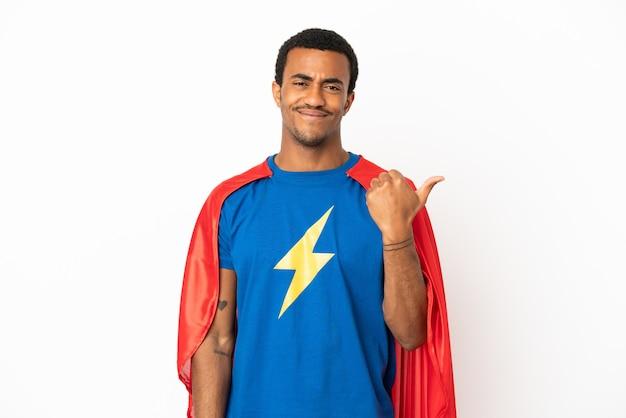 African american super hero man sur fond blanc isolé pointant sur le côté pour présenter un produit