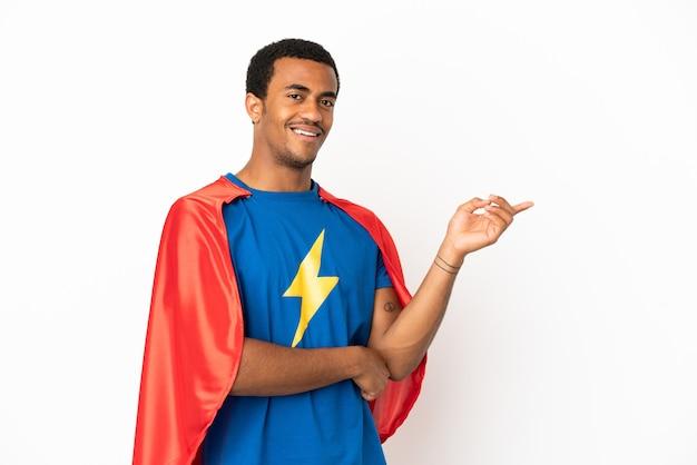 African american super hero man sur fond blanc isolé, pointant le doigt sur le côté