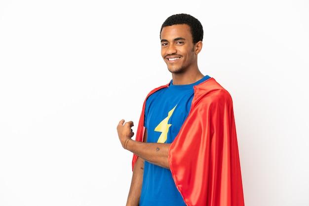 African american super hero man sur fond blanc isolé pointant vers l'arrière