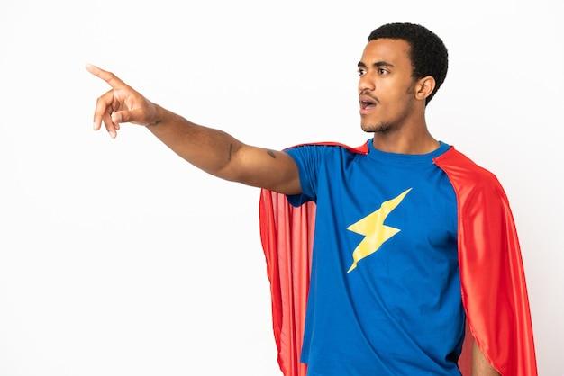 African american super hero man sur fond blanc isolé pointant vers l'extérieur