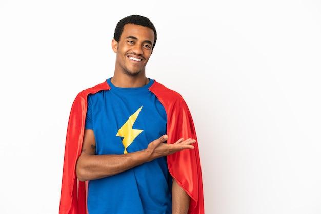 African american super hero man sur fond blanc isolé présentant une idée tout en souriant vers